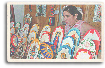 A Hispanic woman displays her colorful santos (retablos) at the annual Spanish Market on the historic Plaza in downtown Santa Fe, New Mexico. The depiction of Saints is theme commonly used in this traditional Spanish art form.